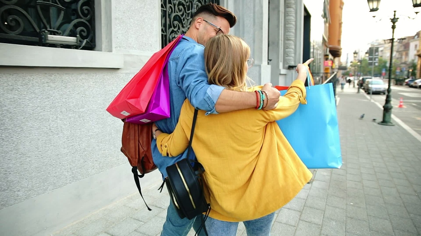 Beautiful young couple walking in and city enjoying in shopping together. | Shutterstock HD Video #1055345792