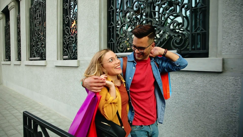 Beautiful young couple walking in and city enjoying in shopping together. | Shutterstock HD Video #1055345795