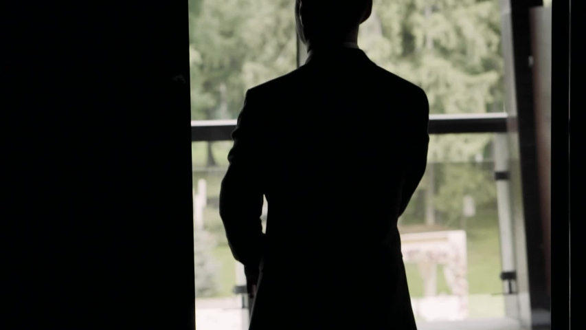 Man puts on a jacket in the backlight. A man is standing near the window and getting dressed