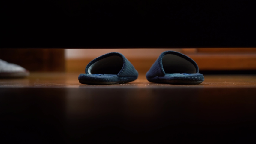 4k, Slippers on the floor.Man's foot put on slippers on the floor and go out. Camera  under the bed. View from under the bed. Royalty-Free Stock Footage #1055346968