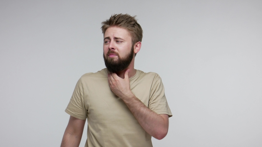 Flu-sick bearded guy suffering sore throat, choked and breathing hard rubbing neck to relieve pain, having respiratory infection with larynx inflammation, tonsillitis. indoor studio shot isolated | Shutterstock HD Video #1055349368