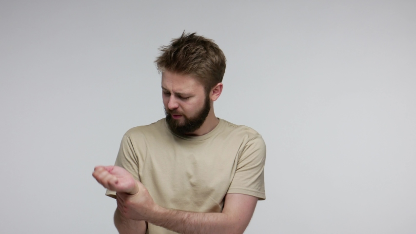 Bearded man moving injured hand, suffering spasm in sore wrist, joint inflammation of rheumatoid arthritis, stiff muscles, carpal tunnel syndrome. indoor studio shot isolated on gray background | Shutterstock HD Video #1055349380