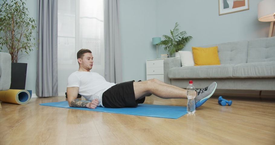 Adult man working out to keep fit, loose weight at home. Attractve sporty guy doing crunches, sit-ups using a bottle of water on mat in the living room. Fitness, gymnastics, aerobics, sports concept.
