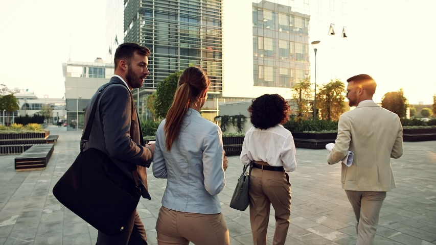 Group of business people walking outside in front of office buildings. | Shutterstock HD Video #1055351105