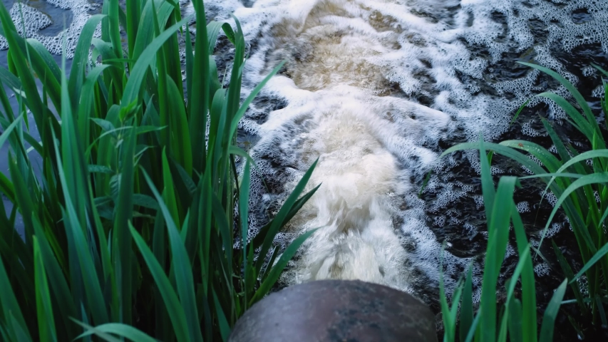 Environmental pollution, ecology problems. Sewer pipe drains dirty water from factory or city into river. Urban industrial waste pollutes water. Drainage tube system flood protection. Royalty-Free Stock Footage #1055353835