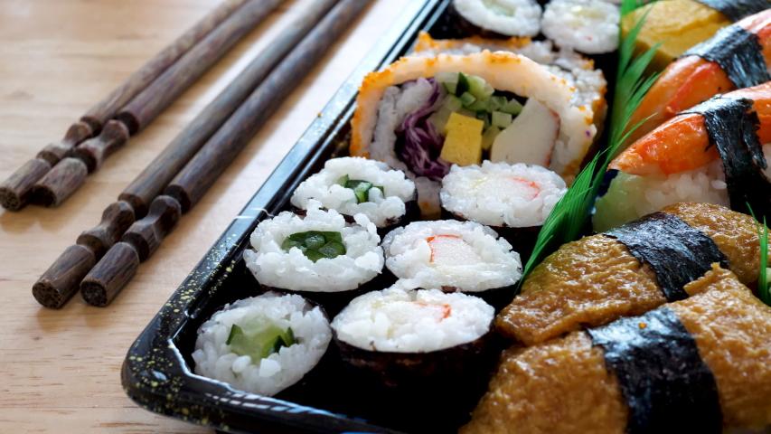 Japanese variation sushi food. Delicatessen food. Eating together appetizer concept. Roll, uramaki, hosomaki and nigiri | Shutterstock HD Video #1055355227