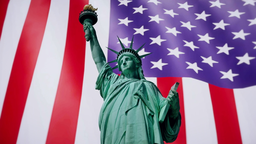 Inspirational footage of the Statue of liberty in front of the United States of America flag blowing in the wind behind - seamless looping. | Shutterstock HD Video #1055355938