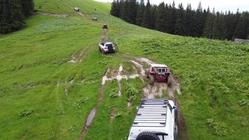Several SUVs are driving along a mountain road along a dirt road. Aerial view. | Shutterstock HD Video #1055357039