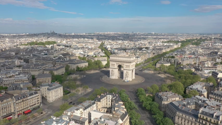 France, Paris Arc de Triomphe (Triumphal Arch) in Champs Elysees with Sacré-Coeur Basilica church in the background. Summer day. Aerial view from right to left (looks like helicopter or drone shot). | Shutterstock HD Video #1055357072