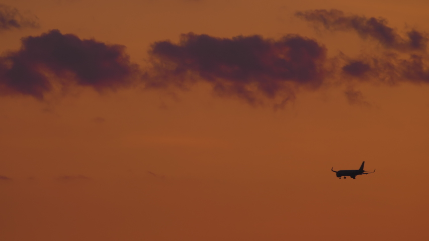 Airplane on the final approach before landing on the background of the sunset dusk sky   Shutterstock HD Video #1055359403