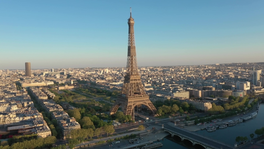 Paris drone, France, Tour Eiffel tower at sunset or sunrise with Champ-de-Mars garden. 4k quality drone shot, aerial view above Seine river from right to left