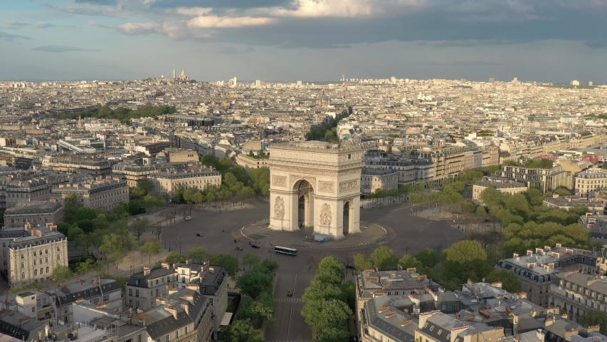 France, Paris Arc de Triomphe (Triumphal Arch) in Champs Elysees, at sunset (or sunrise). 4k quality drone shot, aerial view from right to left | Shutterstock HD Video #1055360258