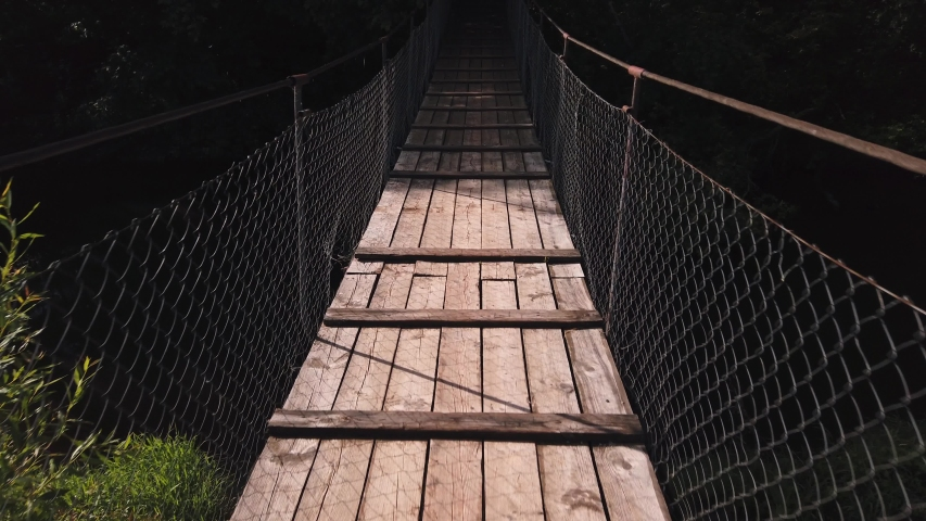 Old wooden hanging cable bridge in countryside. The camera moves forward | Shutterstock HD Video #1055360363