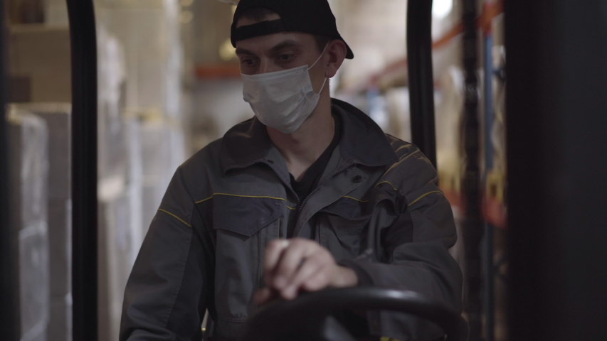 Portrait of confident serious Caucasian driver driving warehouse loader. Young handsome male employee in face mask working at factory storage on Covid-19 pandemic. Transporting, logistics.