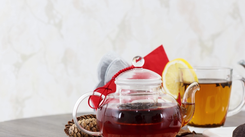 Cup of black tea with tea kettle and sweet biscuits on table background. | Shutterstock HD Video #1055362715