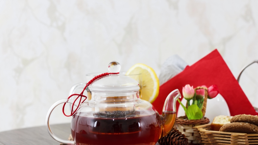 Cup of black tea with tea kettle and sweet biscuits on table background. | Shutterstock HD Video #1055362733