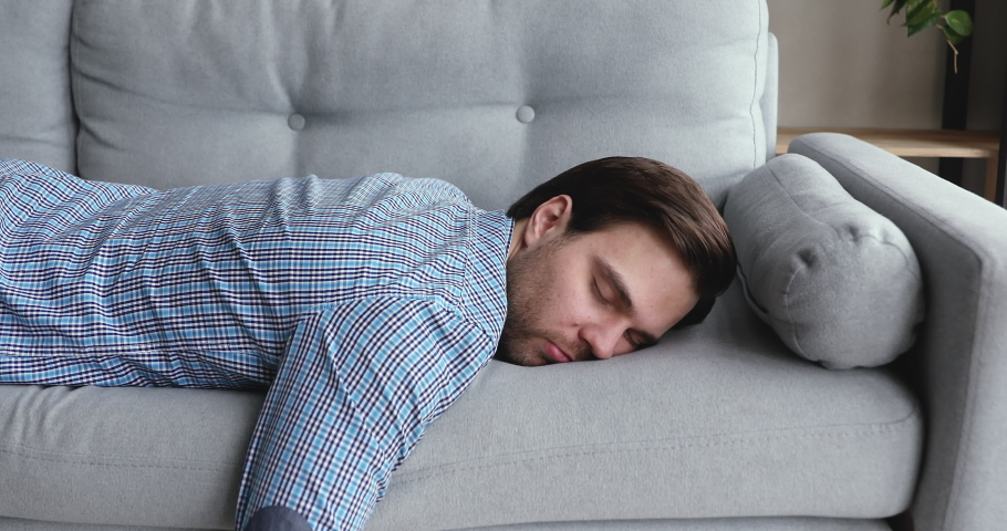 Exhausted overloaded young man in casual shirt came home after work flopped down on sofa feels like squeezed lemon. Concept of after party, tired overworked person hard day, lack of energy, breakdown | Shutterstock HD Video #1055363120