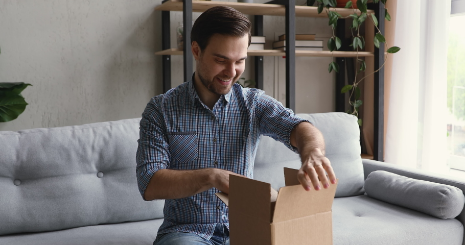 Man sit on sofa open delivered parcel sincerely glad on-line shop purchased goods through internet. Good, qualified services, easy fast delivery. Trusted transport company, satisfied client of e-store
