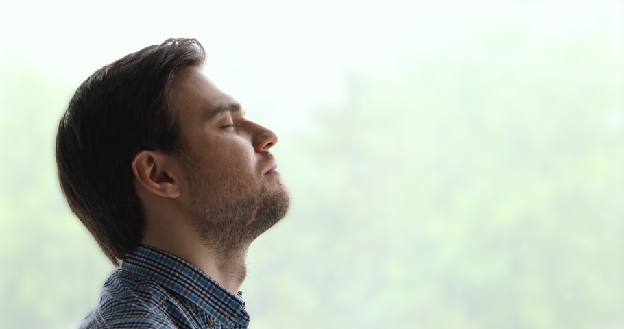 Peaceful man pose aside near window background closed eyes breath fresh air feels calm. Anxiety relief, brings internal state in order exercise, close up side view face. No stress, mindfulness concept | Shutterstock HD Video #1055363129