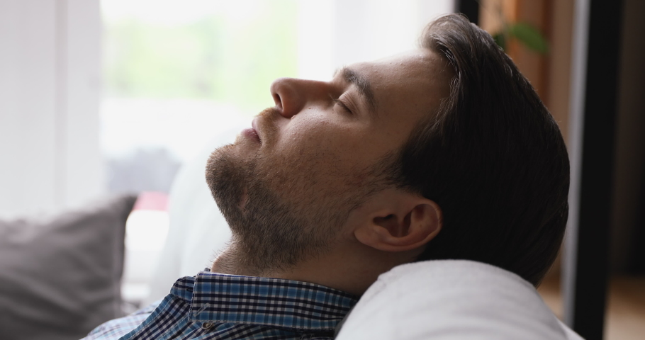 Close up side tranquil man view face closed eyes fall asleep lying leaned on couch soft cushion, reduce fatigue, breath air-conditioned humidifier fresh air feels calm. No stress, repose break concept | Shutterstock HD Video #1055363135