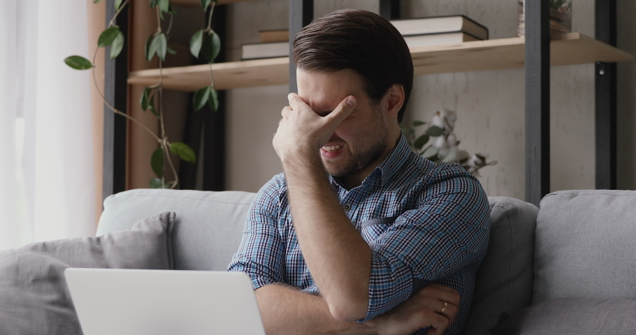 Man sitting with laptop received badly news feels frustrated cover face with palm looks very disappointed lost document works unsaved project, problems with device, unpleasant news by e-mail concept