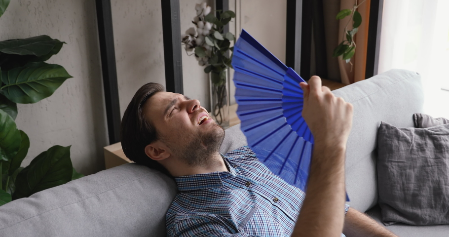 Overheated man lying on couch at hot summer weather day feels unwell discomfort sweaty suffers from heat wave blue fan cooling himself, dwelling without air conditioner need climate control concept