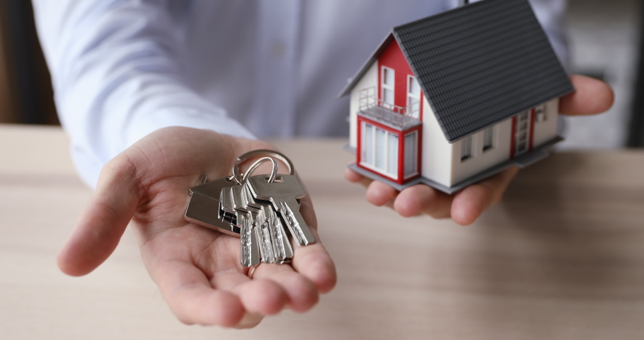 Close up view realtor agent man hand hold bunch of keys and tiny house model home layout. Real estate purchase, new paid property ownership, construction company make special offer to client concept | Shutterstock HD Video #1055363198