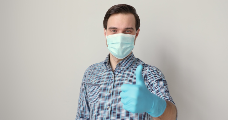 On gray studio background man wears medical face mask protective rubber gloves on hands showing thumbs up gesture, caution preventive, measures due covid-2019, approve symbol, positive opinion concept
