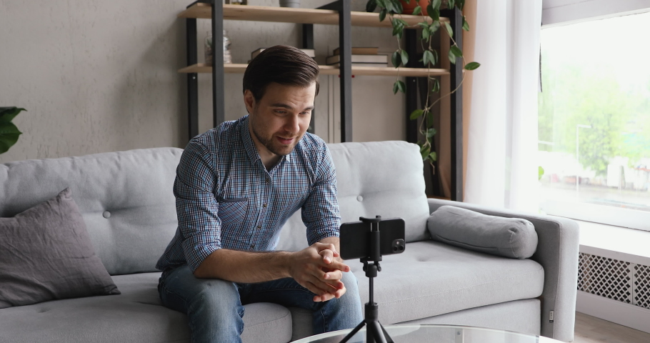 Man record videovlog using smart phone seated on couch alone in living room, put device on tripod guy film new vlog make on-line live stream, lead webinar distant chat, modern tech video event concept Royalty-Free Stock Footage #1055363315