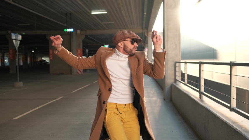 Cheerful and happy young man with beard actively dancing while walking down the street on sunset background. He's wearing a brown jacket. Urban concrete park next to business center. Sunny. | Shutterstock HD Video #1055363486