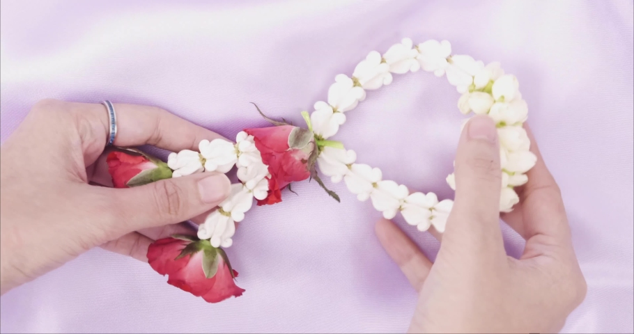 Fresh jasmine, roses and mexican marigold in a circle row, part of traditional garland in Thailand in hand s and putting it on purple fabric as background. | Shutterstock HD Video #1055364080