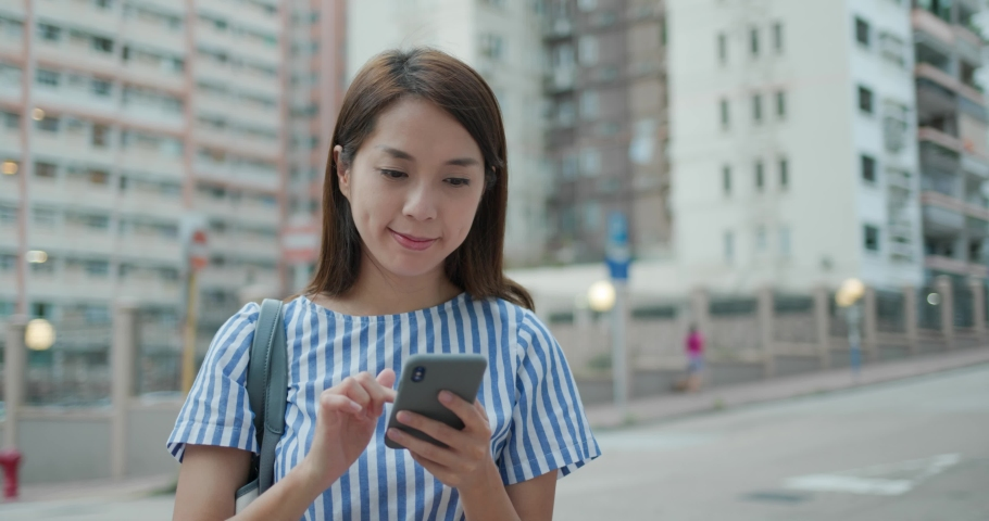 Woman use of mobile phone in city | Shutterstock HD Video #1055364359