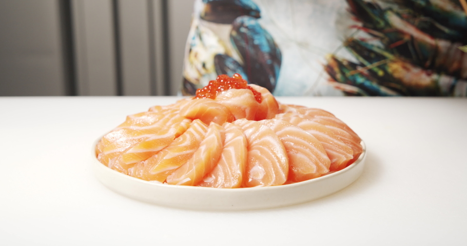 Close-up of cook's hands decorating greens a dish of slices of salmon and red caviar on a plate | Shutterstock HD Video #1055364836