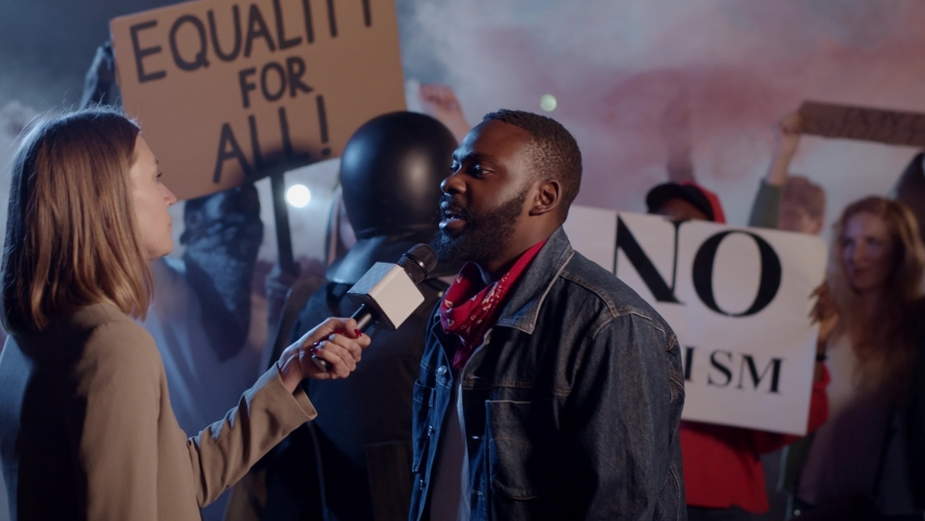 Afro-American Determined Activist Leader Giving Interview Public Speech On-Air on TV Outside. Multi-Racial Young People Protesting Against Cops Cruelty.