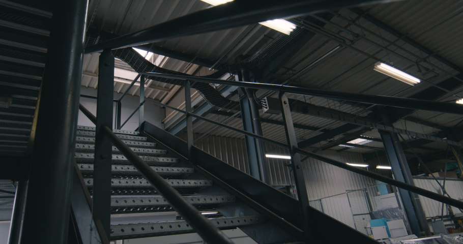 Metal staircase in a factory with white neon lights on the ceiling | Shutterstock HD Video #1055365256