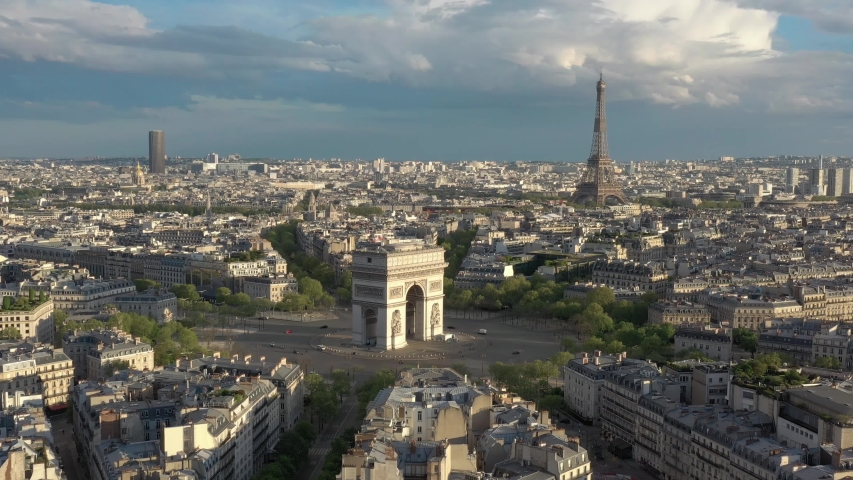 France, Paris Arc de Triomphe (Triumphal Arch) in Champs Elysees and Eiffel tower behind, at sunset (or sunrise). 4k Quality shot, forward drone shot, aerial view