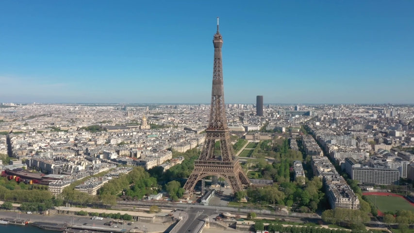 France, Paris Tour Eiffel (Eiffel Tower) in summer day, with Champs-de-Mars garden and Montparnasse tower. Long drone shot, aerial view above Seine river from right to left | Shutterstock HD Video #1055365355