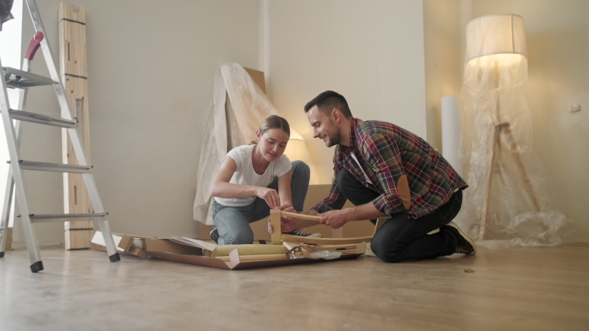 Happy Smiling Couple Collects Furniture as a Team. Girl Helps to Assemble Chair Details. Female Tightens Bolt. Moving to New Apartment, Young Family Assemble Furniture | Shutterstock HD Video #1055366678