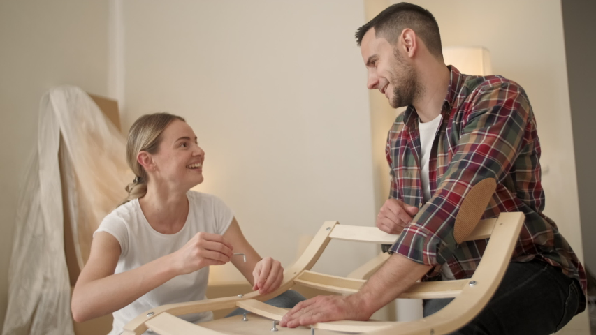 Happy Smiling Couple Collects Furniture as a Team. Girl Helps to Assemble Chair Details. Female Tightens Bolt. Moving to New Apartment, Young Family Assemble Furniture | Shutterstock HD Video #1055366681