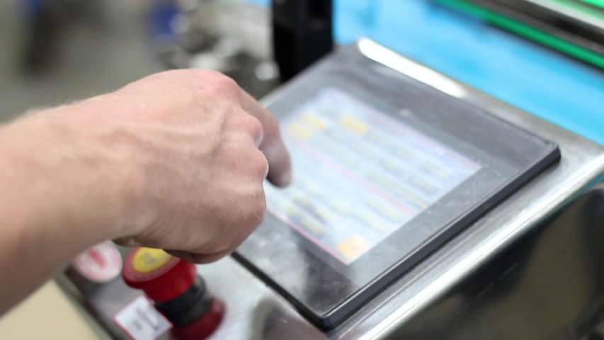 Worker's hand at the factory leads a finger on a touch monitor | Shutterstock HD Video #1055367083