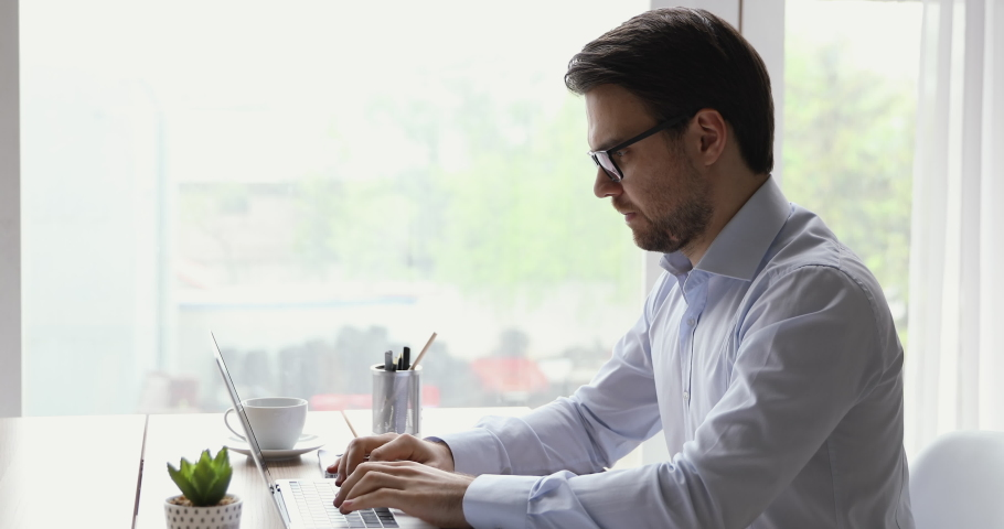 Side view businessman in formal shirt sit at desk near window typing on laptop making research prepare report thinking solving search solution learn new application feels assembled busy during workday | Shutterstock HD Video #1055367782