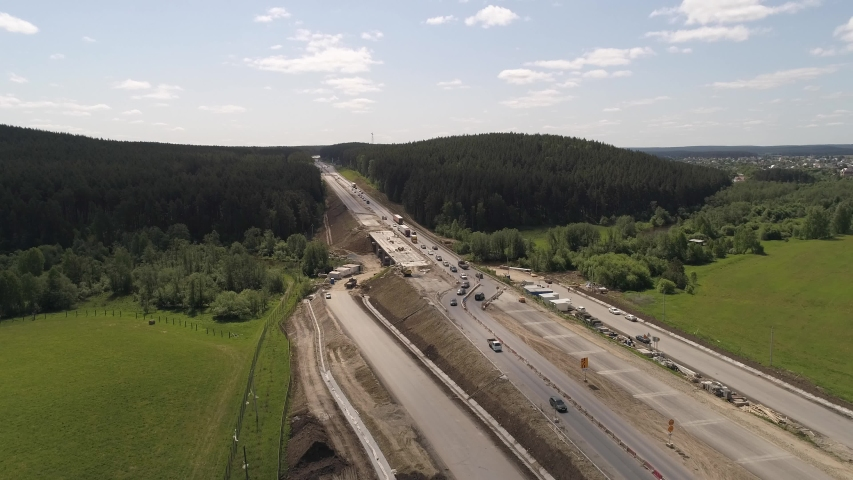 Aerial view of construction works of a highway section. Cars are going from both sides. The scheme of transport movement has changed. The road goes through the forests and fields near the village. A s | Shutterstock HD Video #1055367851