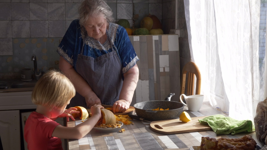 Funny blond boy helps gray-haired grandmother in kitchen. elderly woman cuts and puts pumpkin in frying pan. kid goes through and cleans pumpkin seeds. Child and granny are happy together | Shutterstock HD Video #1055368004
