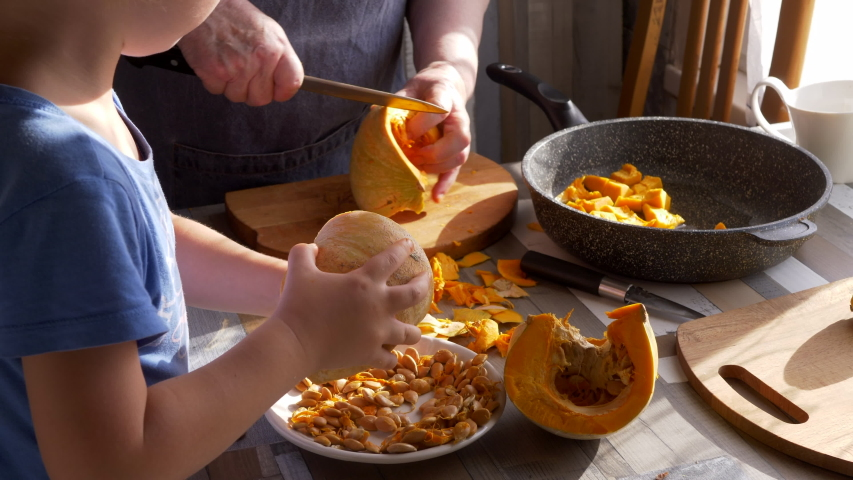 Funny blond boy helps gray-haired grandmother in kitchen. elderly woman cuts and puts pumpkin in frying pan. kid goes through and cleans pumpkin seeds. Child and granny are happy together | Shutterstock HD Video #1055368007