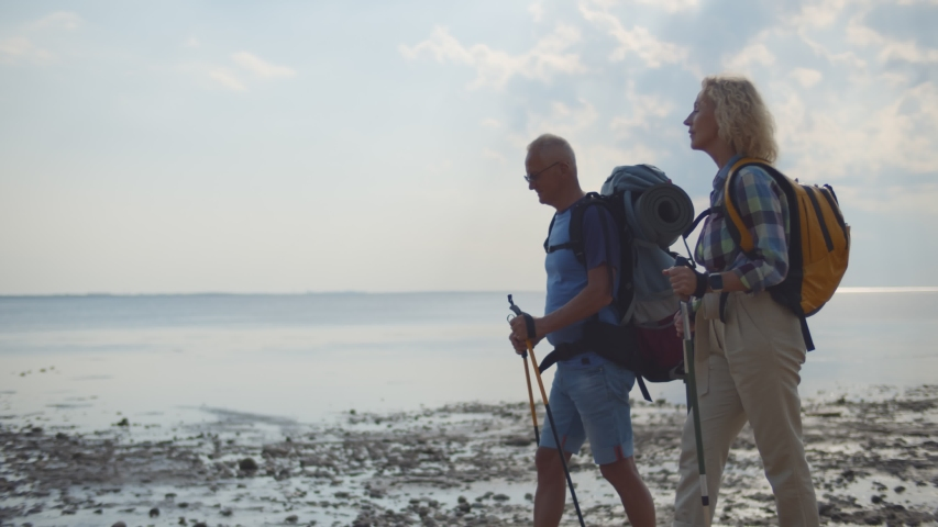 Modern senior couple with backpacks trekking on sandy beach with seascape background. Side view of active aged husband and wife nordic walking on lake shore | Shutterstock HD Video #1055368244