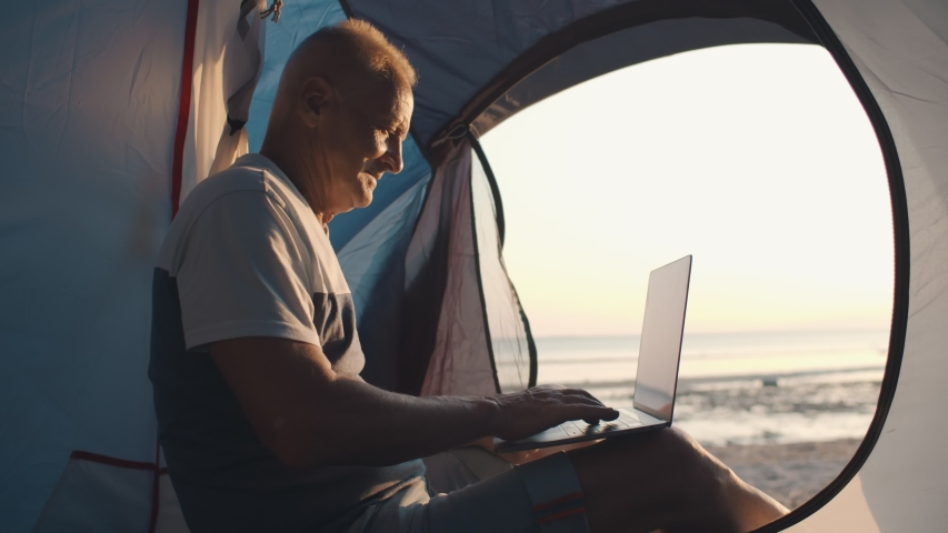 Side view of senior man working on laptop sitting in tent on beach. Retired tourist planning next day trip on computer enjoying sunrise ocean view camping on beach | Shutterstock HD Video #1055368250