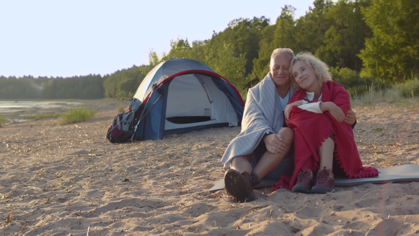 Romantic aged couple relaxing near tent on beach, hugging and admiring landscape. Portrait of mature man hugging beautiful wife wrapped in blanket sitting on sand together during camping trip | Shutterstock HD Video #1055368268