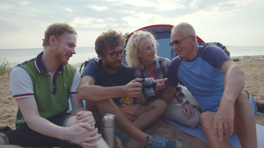 Smiling family with photo camera camping on lake shore on holidays. Portrait of cheerful retired parents and adult sons sitting on beach near tent and watching traveling photos on digital camera. | Shutterstock HD Video #1055368271