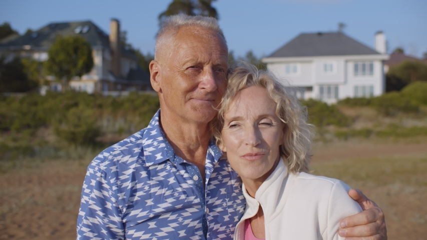 Happy senior couple hugging on sandy beach over country house background. Portrait of loving retired husband and wife embracing and relaxing on beach. Happy and successful retirement concept | Shutterstock HD Video #1055368277