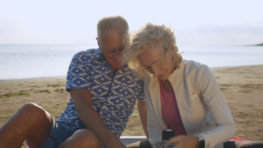 Happy senior couple sitting on plaid with thermos bottle on summer beach. Portrait of mature husband and wife relaxing on lake shore having picnic and drinking hot tea from thermos flask | Shutterstock HD Video #1055368283